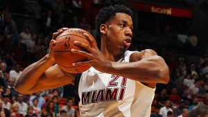 hassan whiteside holding a basketball in a Miami Heat uniform